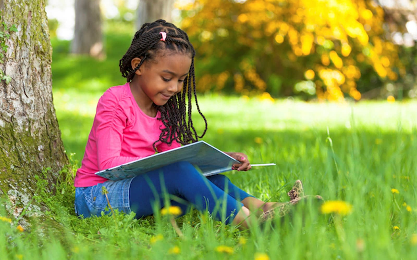 young black girl reading book under tree