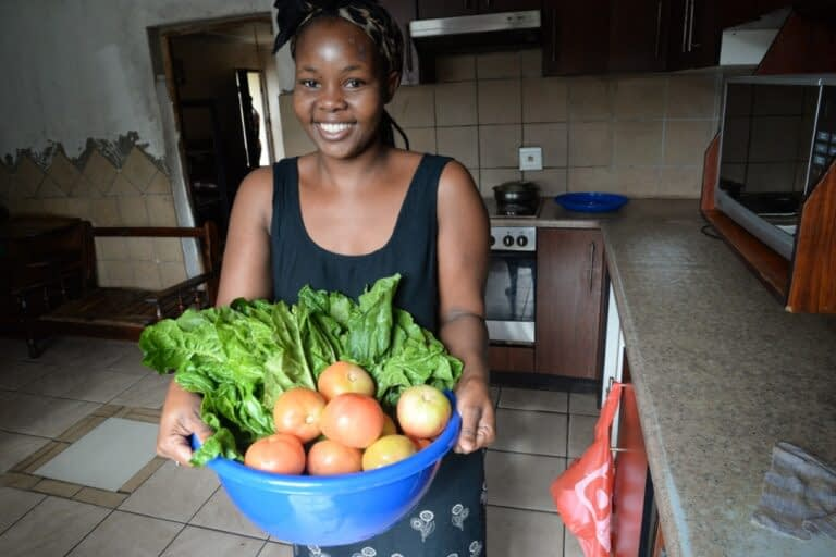 Sphile Mbhize holds a bowl of vegetables